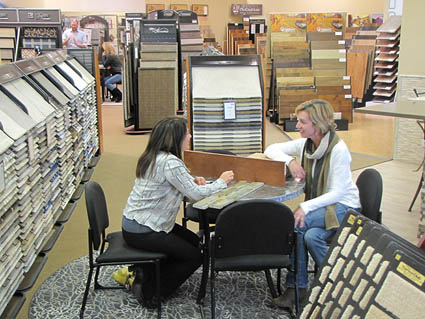 A Floor Club Specialist helps a customer with her flooring selection.